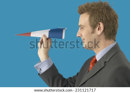 Businessman Holding Paper Plane Made from French Flag - stock photo