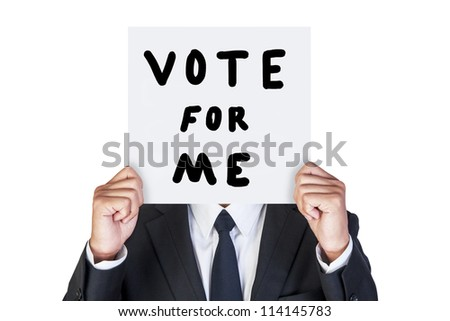Businessman holding paper that say vote for me - stock photo
