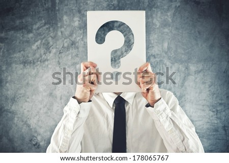 Businessman holding paper with printed question mark in front of his face - stock photo
