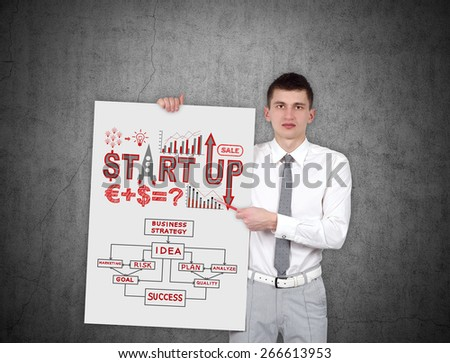 businessman holding placard with start up scheme - stock photo