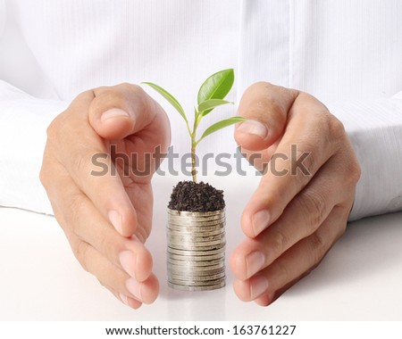 Businessman holding plant sprouting from a handful of coins - stock photo