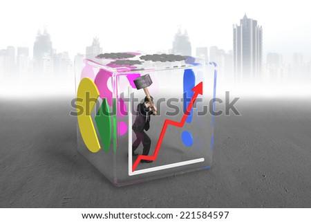 businessman holding sledgehammer to break glass cube on city skyscraper background - stock photo