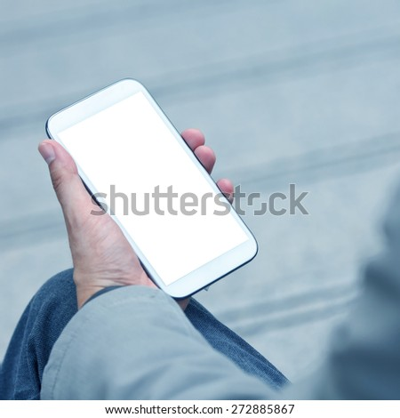 Businessman holding smart phone with empty screen - stock photo