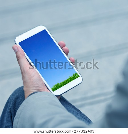 Businessman holding smart phone with green natural background. - stock photo