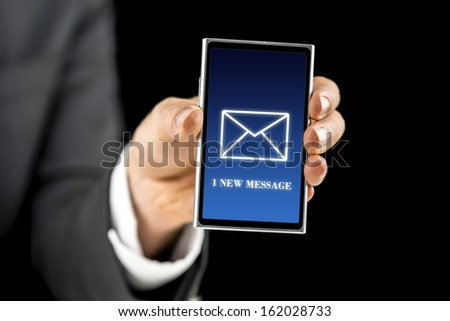 Businessman holding smartphone with 1 new message sign on screen. Over black background. - stock photo