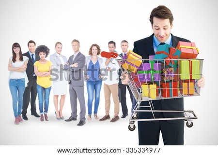 Businessman holding something with his hands against trolley full of gifts - stock photo