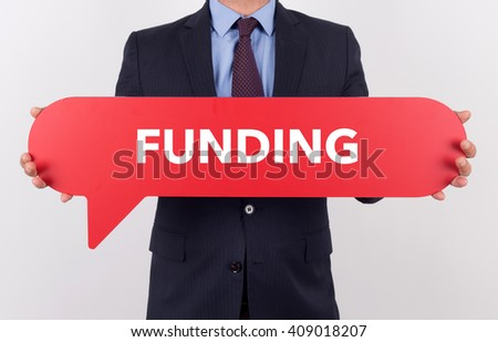 Businessman holding speech bubble with a word FUNDING - stock photo