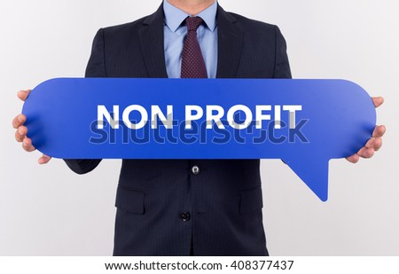 Businessman holding speech bubble with a word NON PROFIT - stock photo