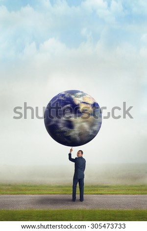 businessman holding spinning planet earth aloft with one finger subtle vintage filter and selective focus with copy space  - stock photo