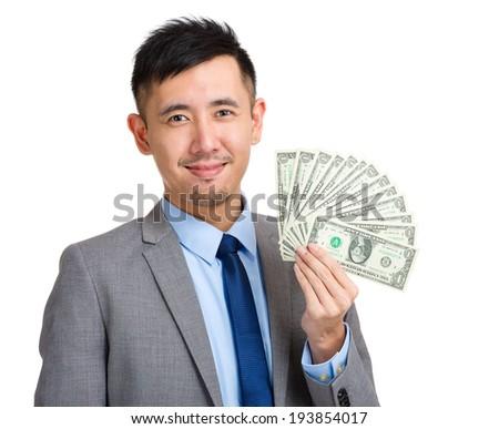 Businessman holding spread of money - stock photo