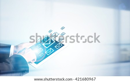 Businessman holding tablet with email icons on bright background - stock photo