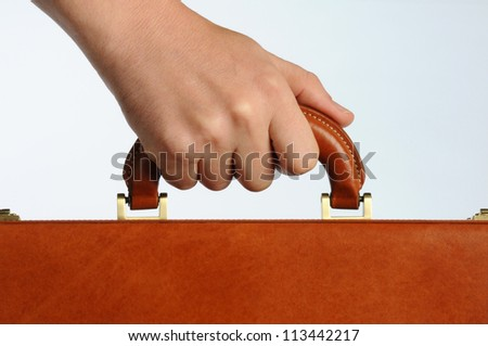 businessman holding the handle of a brown leather briefcase - stock photo