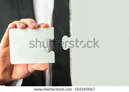 Businessman holding the missing piece to complete the puzzle in his hand conceptual of the solution to a problem or completing a task. - stock photo