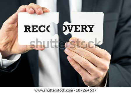 Businessman holding the word Recovery split over two puzzle pieces in his hands conceptual of overcoming challenges and finding solutions leading to a recovery in the business. - stock photo
