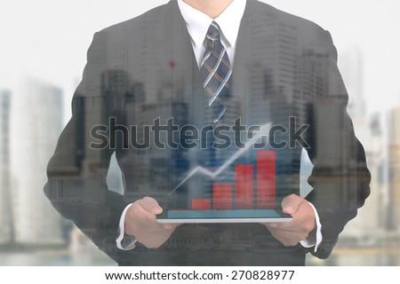 Businessman holding touch pad for show case growing graph  - stock photo