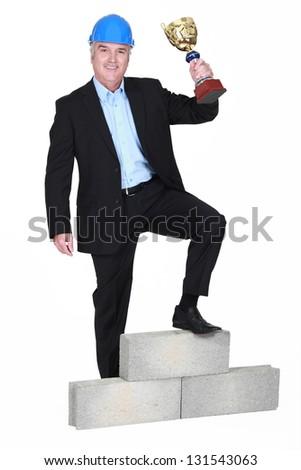 Businessman holding trophy - stock photo