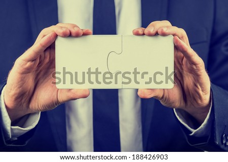 Businessman holding two blank white interlocked puzzle pieces with copyspace for your text conceptual of teamwork, problem solving or meeting a business challenge, close up view with a vintage effect. - stock photo