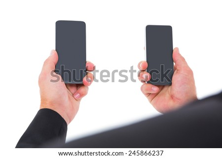 Businessman holding two smart phones on white background - stock photo