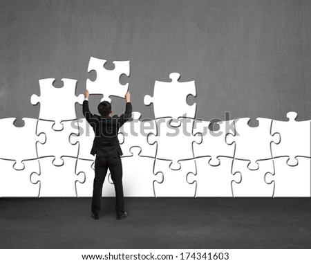 Businessman holding white puzzle to assembly on concrete wall - stock photo
