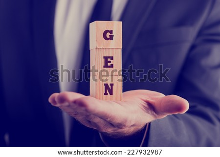 Businessman holding wooden alphabet blocks reading - Gen - balanced in the palm of his hand, toned retro effect. - stock photo