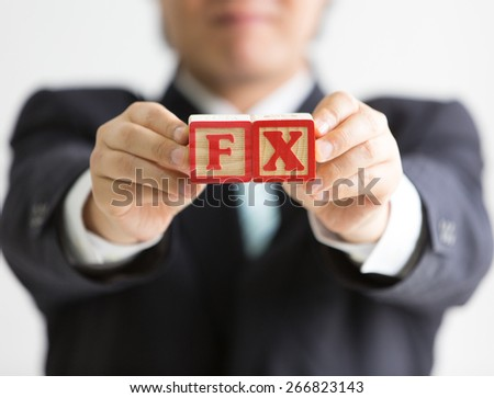 Businessman holding wooden blocks with etched letters F and X (abbreviation for foreign exchange market) - stock photo