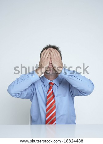 businessman holds his face in his hands - stock photo