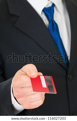 Businessman holds out a credit card. Closeup. - stock photo