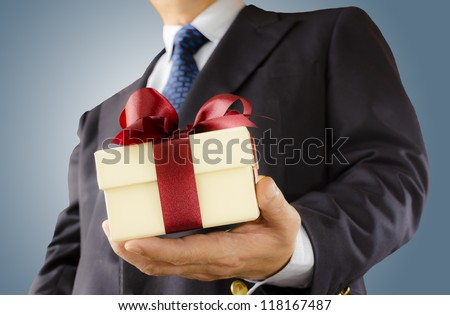 Businessman holds out the gift box ,isolated background - stock photo