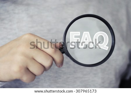 Businessman holds search loupe magnifier FAQ button - stock photo