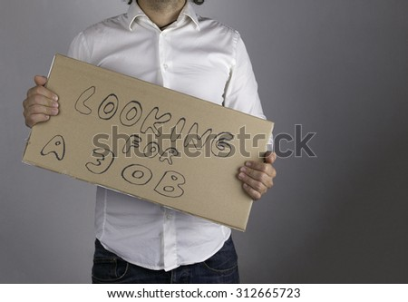 Businessman holds the inscription - Looking for a job - stock photo