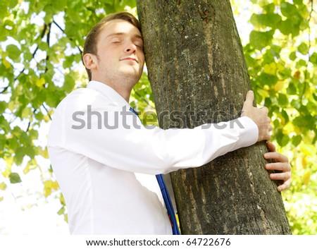 Businessman hugging tree - stock photo