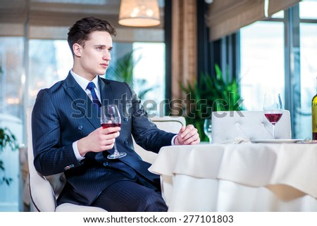 businessman in a bar. Confident businessman in formal wear sitting at a table in a restaurant while holding a glass of wine and looking ahead - stock photo