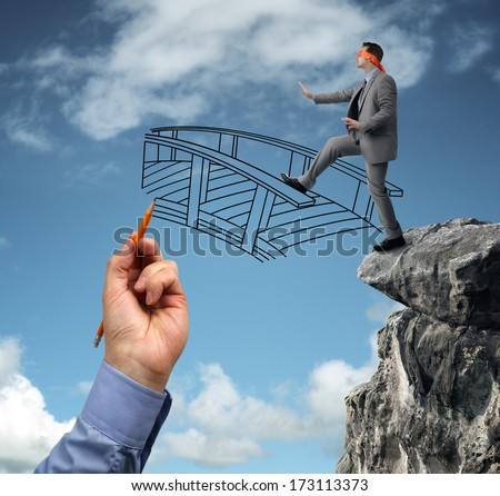 Businessman in a blindfold stepping off a cliff ledge with giant hand drawing a bridge for a safe crossing concept for building bridges, risk, challenge, conquering adversity, ignorance and assistance - stock photo