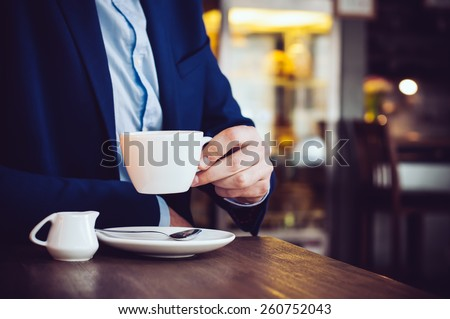 Businessman in a blue jacket with a cup of coffee in the cafe at the table, close-up - stock photo
