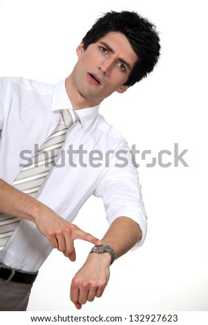 businessman in a hurry pointing at his watch - stock photo
