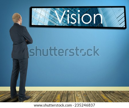 businessman in a room looking at a wall of which is the frame with inscription Vision - stock photo