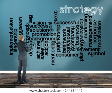 businessman in a room looking at a wall of which is the wordcloud related to strategy - stock photo