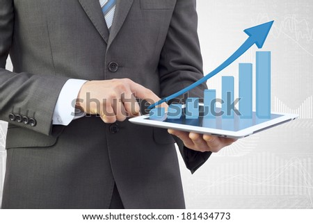 Businessman in a suit holding a tablet pc. Growth chart on screen tablet - stock photo