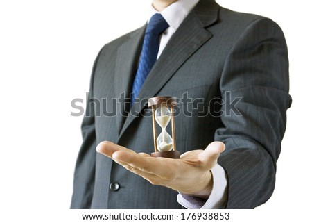 Businessman in a suit holding hourglass isolated on white background - time is money concept - stock photo