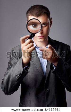 businessman in a suit looking through a magnifying glass - stock photo