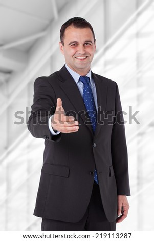Businessman in a suit reaching hand for handshake. Isolated with work path. - stock photo