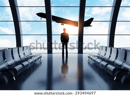 businessman in airport looking on airplane in sky - stock photo