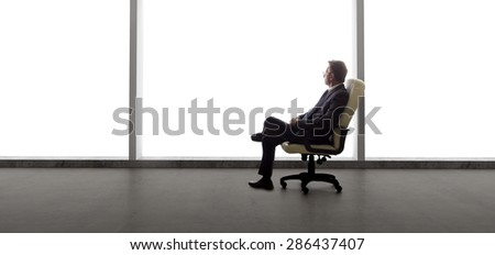Businessman in an empty office for a startup business or a failed entrepreneur with an empty office due to bankruptcy.  The lonely mood is set by the back light from the windows  - stock photo
