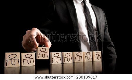Businessman in black and white business suit arranging wooden pieces with people drawings on the table with pure black background. Simple human resource concept. - stock photo