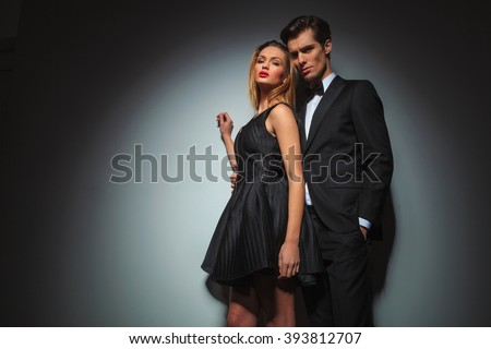 businessman in black standing with hand in pocket while embracing woman in black dress from behind. woman raised one hand while looking at the camera in gray studio background - stock photo