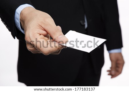 Businessman in black suit and a blue shirt with a blue tie, shows business card with copy space, shallow dept of field, isolated on a grey background - stock photo