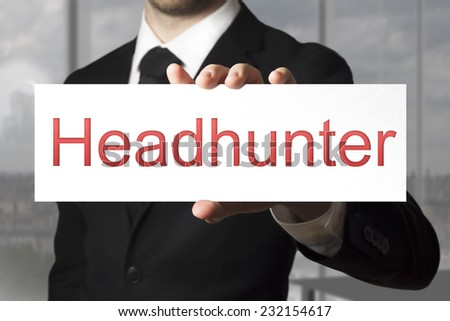 businessman in black suit holding white sign headhunter - stock photo