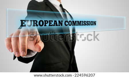 Businessman in Black Suit Pointing Glowing European Commission Texts on Glass. Isolated on Gray Background. - stock photo