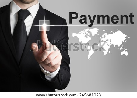 businessman in black suit pushing button payment international service - stock photo