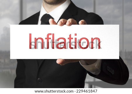 businessman in black suit showing sign inflation fiscal crisis - stock photo